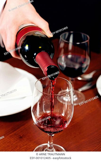 Kellnerin füllt Glas nach