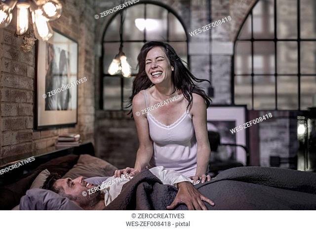 Laughing woman and husband in bed