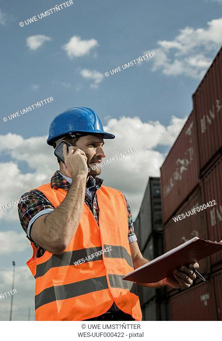 Man with clipboard on the phone at container port