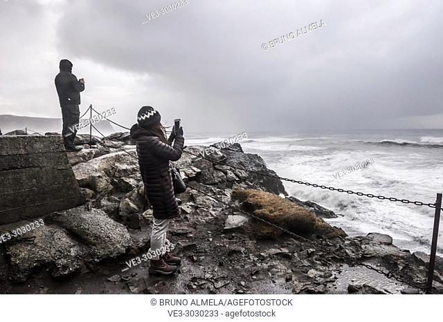 Tourists taking pictures to a rough sea near Kirkjufjara beach (region of Suðurland, Iceland)