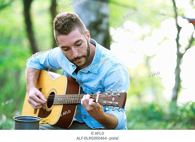 Caucasian man playing guitar at a camp site