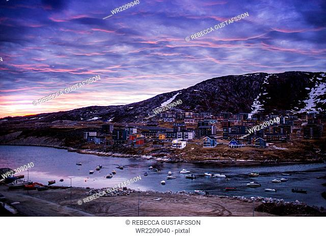 High angle view of residential district by river against dramatic sky during winter