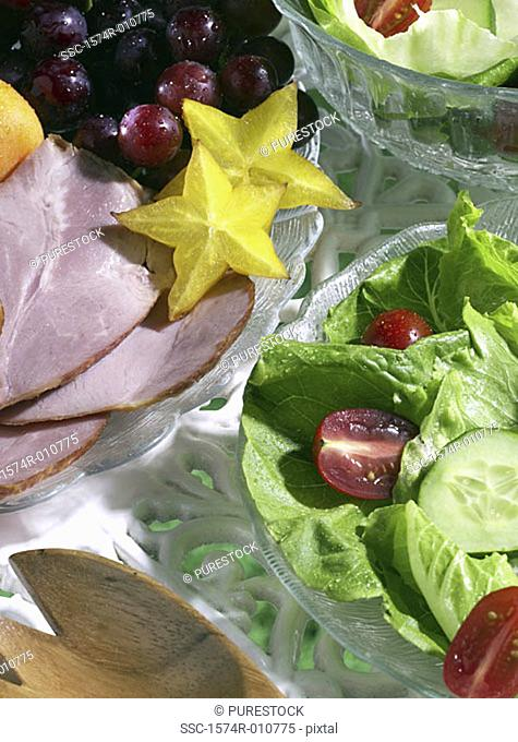 Close-up of a green salad served with sliced meat and fruits