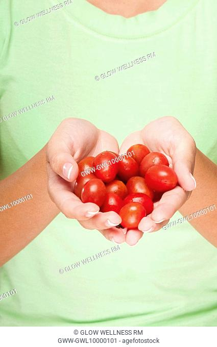 Close-up of a woman holding cherry tomatoes