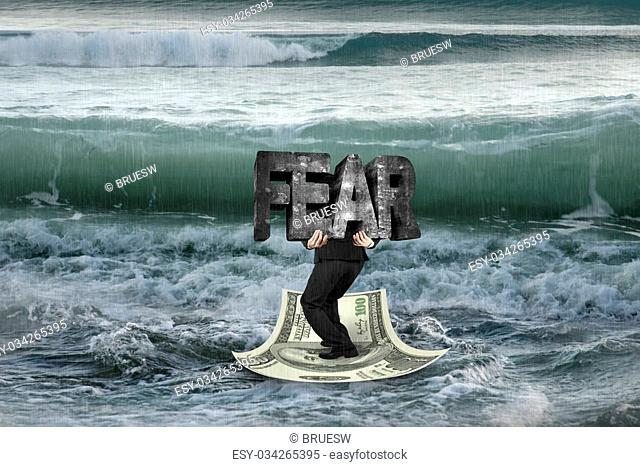 Businessman carrying old concrete structure of FEAR on money boat in sea with wave coming
