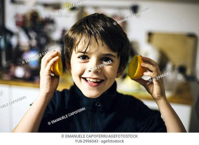 Boy plays with orange peels