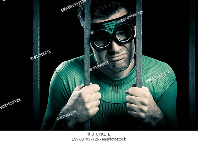 Depressed superhero leaning to prison bars and looking sadly at camera