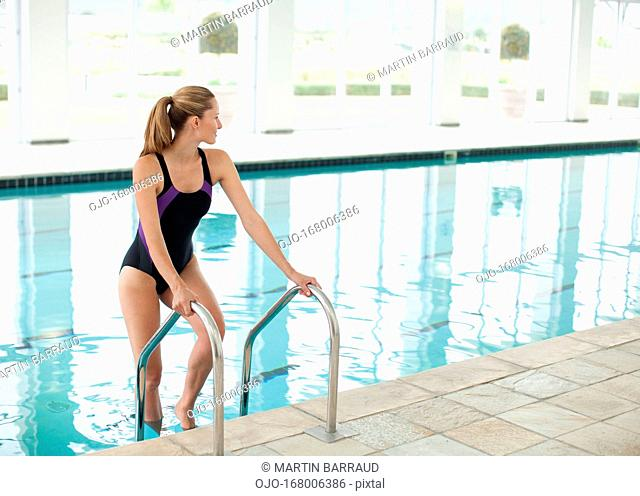 Portrait of smiling woman standing on ladder in swimming pool