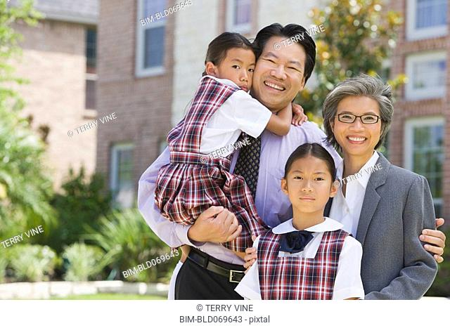 Asian family hugging and smiling outdoors