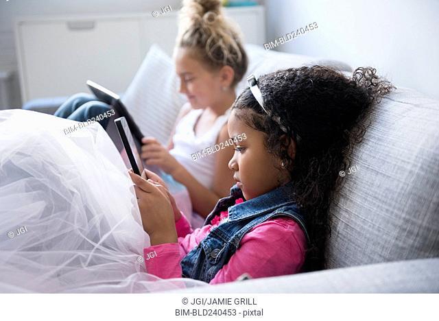 Girls using digital tablets on sofa