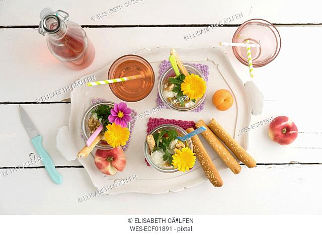 Salad to go in jars, bread sticks and glass of lemonade on tray