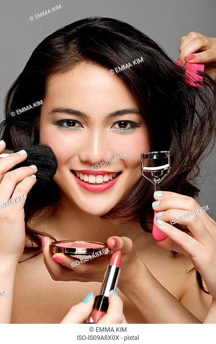 Close up of woman's face surrounded by hands holding make up and beauty equipment