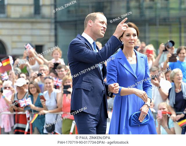 Britain's Prince William (L) and his wife Catherine, Duchess of Cambridge, talk during a visit to the Brandenburg Gate in Berlin, Germany, 19 July 2017