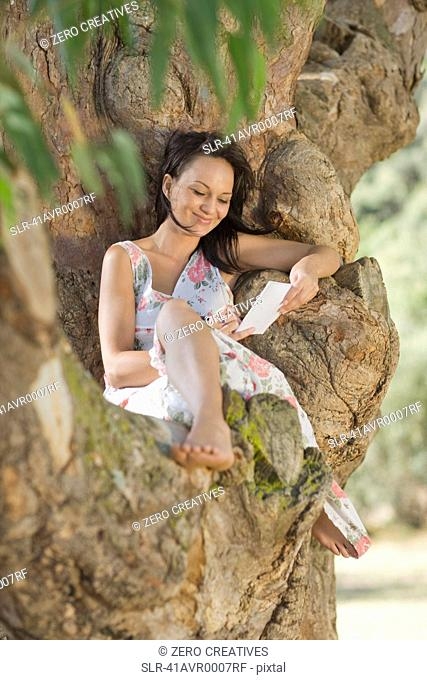 Smiling woman reading in tree