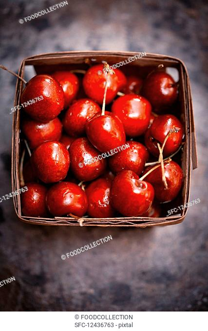 Fresh cherries in a wooden basket (seen from above)