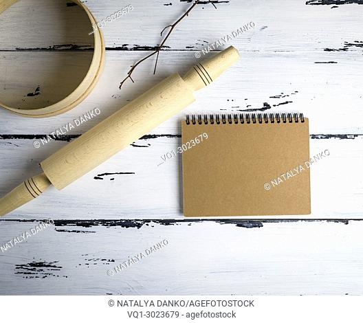 open blank notebook with brown pages and a wooden rolling-pin with a round wooden sieve for flour on a white table, top view