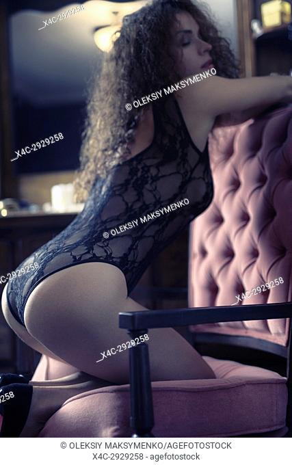 Artistic boudoir portrait of a sexy beautiful woman standing on her knees in a chair leaning against the backrest with her body arched in a seductive curve by a...