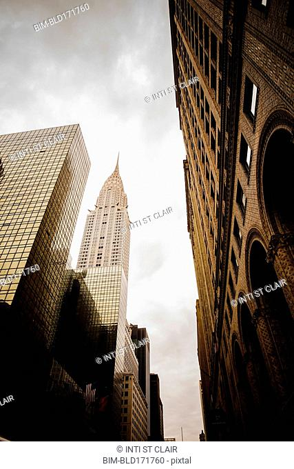 Low angle view of high rise buildings under cloudy sky, New York City, New York, United States