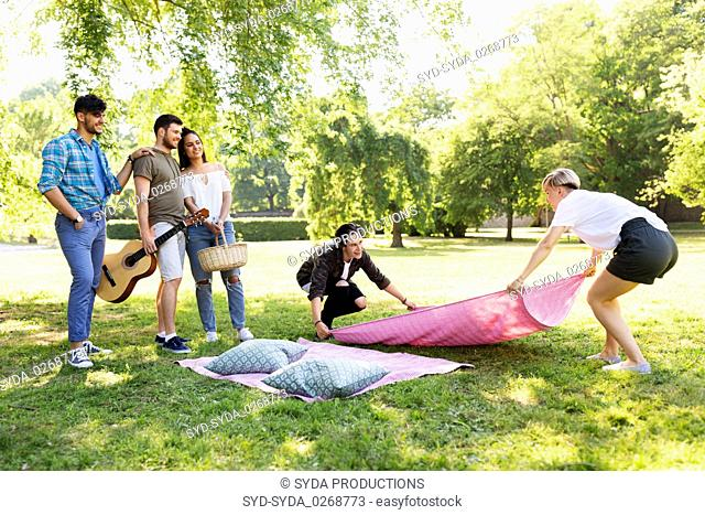 friends arranging place for picnic at summer park
