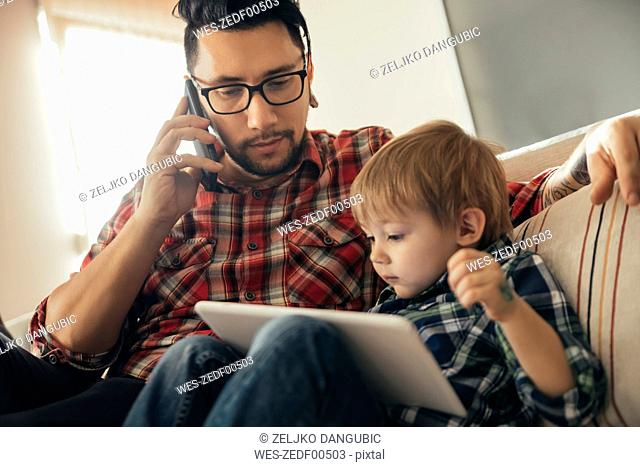 Father and son on couch using tablet and cell phone