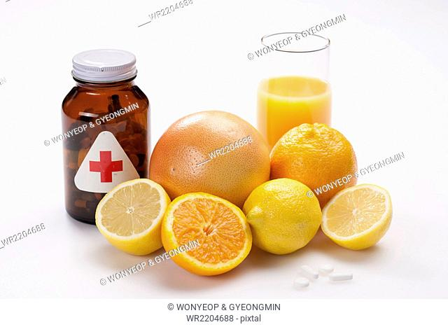 Brown bottle of health supplementary pills with grapefruit, orange, and lemons next and a glass of orange juice with them