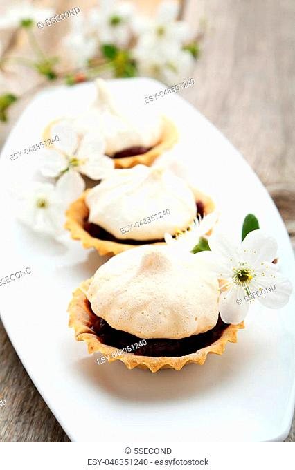 French meringue cookies in tartlet on plate on grey wooden background