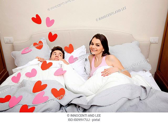Couple in bed with heart shapes on bedclothes
