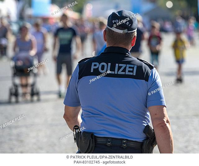 A police officer walks across the grounds of the city festival before the official opening in the centre of Eisenhuettenstadt, Germany, 26 August 2016
