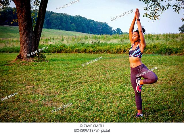 Young woman practicing yoga tree pose in rural park