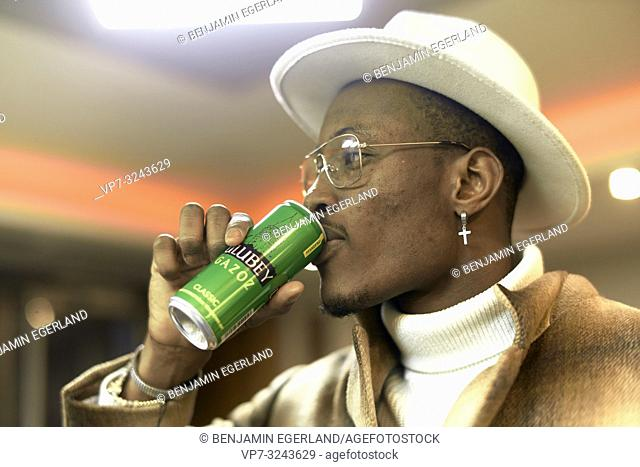 stylish blogger man drinking energy drink indoors in bar, wearing men's fashion clothing outfit, side view headshot, Christian cross earring, in Munich, Germany