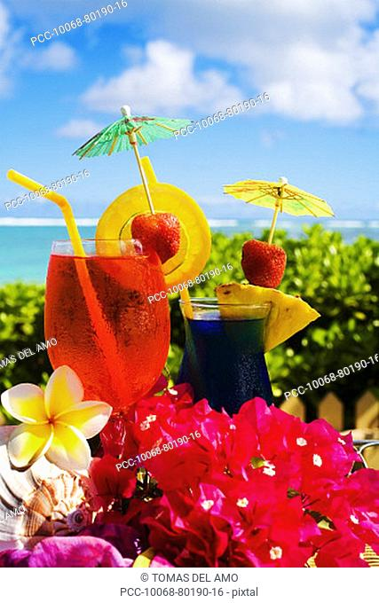Tropical cocktails garnished with flowers and fruit in outdoor setting