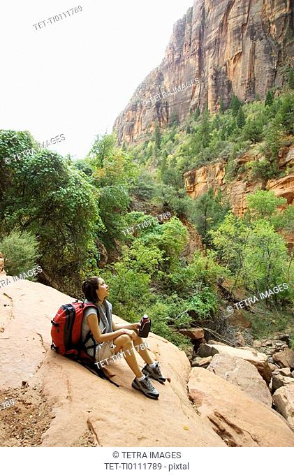 Female hiker resting on a rock