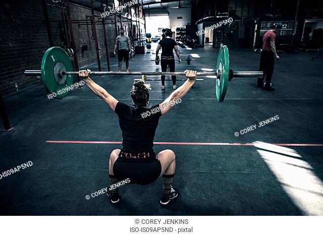 Rear view of young woman crouching with barbell in gym