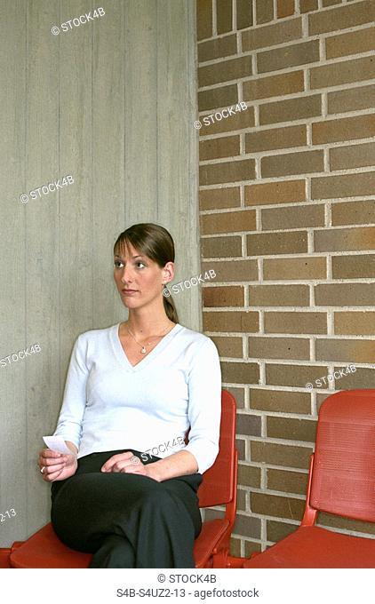 Woman sitting in waiting area of an employment center, holding waiting number