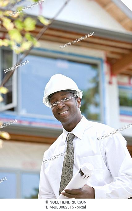 Black architect holding blueprints on construction site