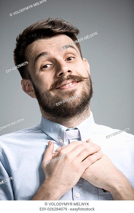 Man wearing a blue shirt is looking imploring. Over gray background