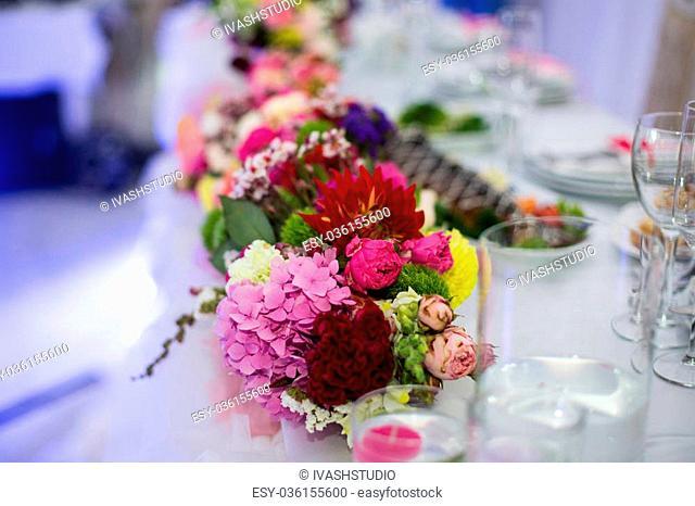 Beautiful freshly cut flowers in a glass vase on wedding reception table closeup