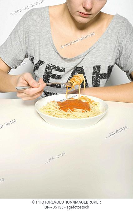 Young woman eating spaghetti