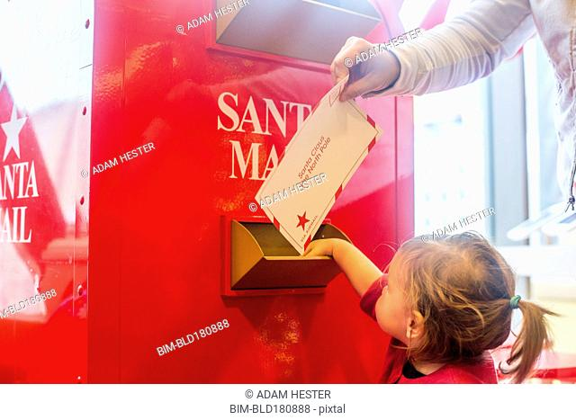 Caucasian mother and daughter mailing letter to Santa
