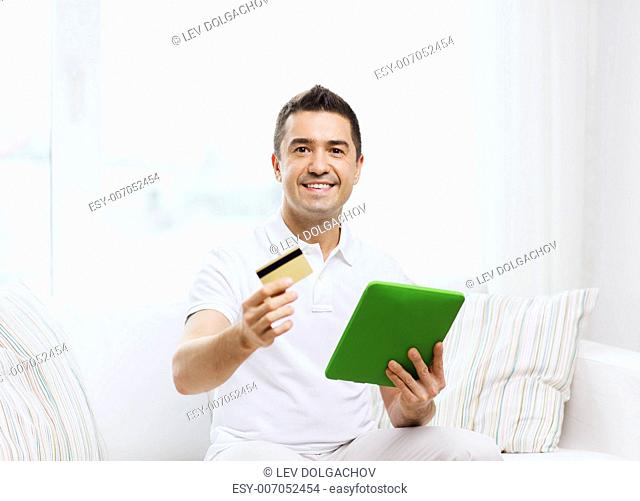 technology, people and lifestyle, distance learning concept - happy man working with tablet pc computer at home