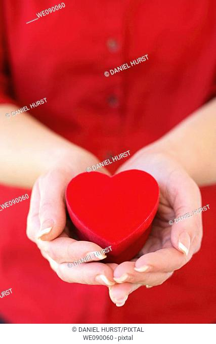 Hands holding heart shaped box