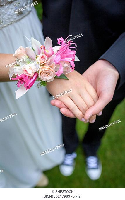 Close up of teenage couple holding hands in prom attire