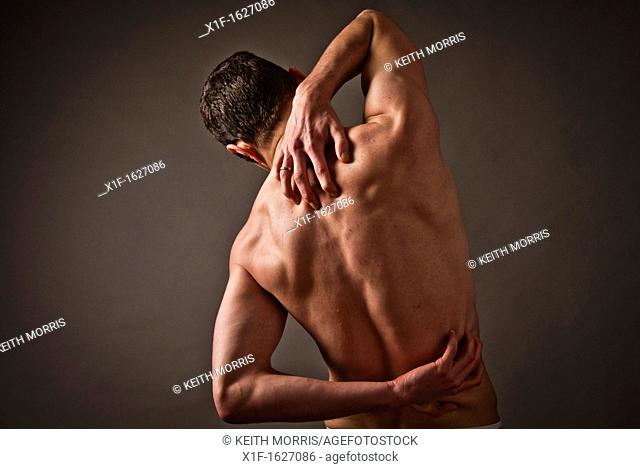 Back ache pain hurt man male person rubbing back