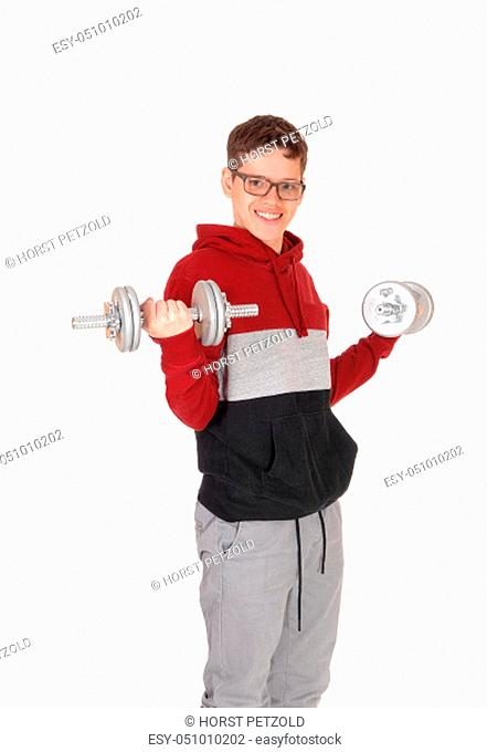 A young smiling teenager boy lifting up two dumbbells wearing a.sweater and jeans, with glasses, isolated for white background