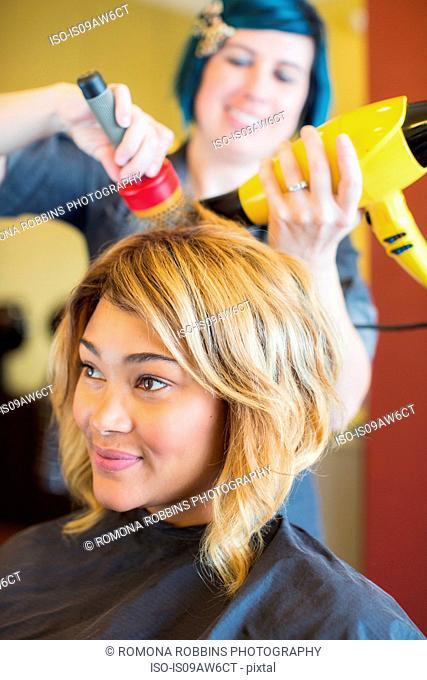 Stylist drying woman's hair in hair salon