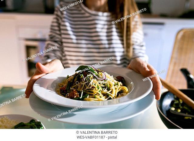Young woman serving vegan pasta dish