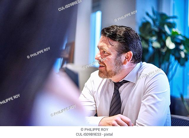 Businessman in office looking away smiling