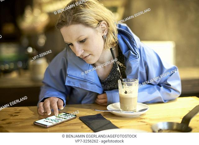 Young woman using smartphone in cafe, Munich, Germany