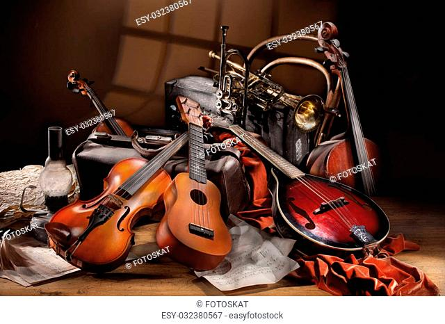 Still life with different musical instruments, notes and old suitcases on a wooden table