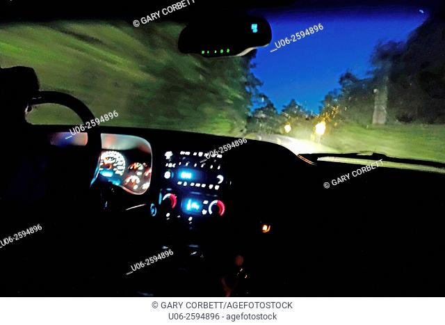 The view through the windshield of a truck driving on a road at night